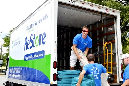 Habitat Spartanburg ReStore Manager Joe Walker unloads patio sets donated by the Carolina Panthers organization.